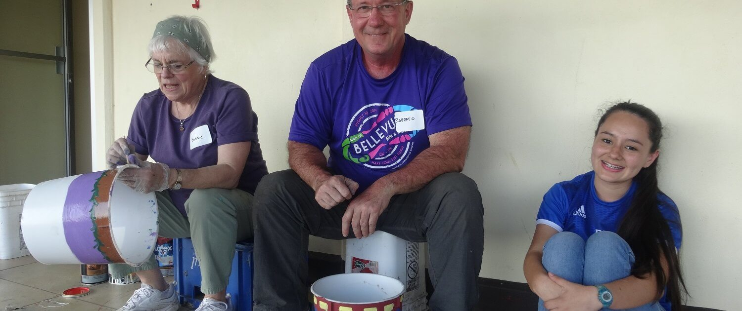 Costa Rica volunteers and student painting ice cream buckets to be used for planters