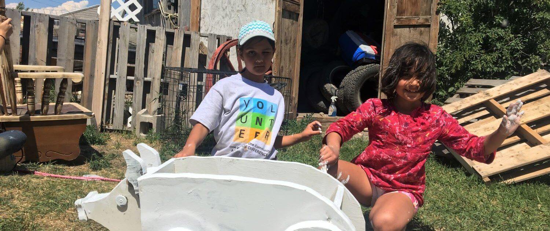 Volunteers Laticia and Savannah paint a mailbox for a local elder blackfeet reservation montana