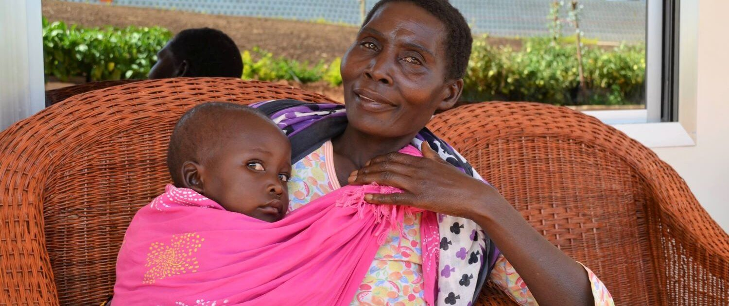 Mom and baby sit outside the RCP center in Ipalamwa, Tanzania.